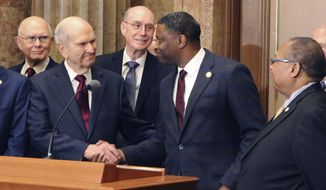 Mormon church President Russell M. Nelson shakes hands with Derrick Johnson, president of the NAACP during a news conference Thursday, May 17, 2018, in Salt Lake City. Top leaders from the NAACP and Mormon church are calling for greater racial harmony and mutual respect following the first official meeting between national leaders from the civil rights organization and Utah-based religion. Johnson said the alliance should serve as an example for others to work in harmony and with greater civility as he read from read prepared remarks during a media event in Salt Lake City Thursday. Nelson called for greater racial and ethnic harmony. (AP Photo/Rick Bowmer)