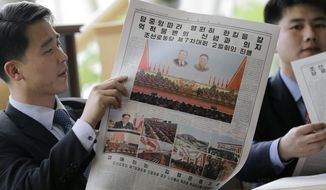 FILE - In this May 8, 2016, file photo, North Koreans read their leader Kim Jong Un's speech published in the local newspaper in Pyongyang, North Korea. Donald Trump and Kim Jong Un have one big thing in common as they prepare for what would be the first ever U.S.-North Korea summit: They both claim to deserve total credit. In a country where there is no Twitter but lots of fake news, North Koreans are getting a very different take on what got the two leaders to agree to meet next month in Singapore. (AP Photo/Kim Kwang Hyon, File)