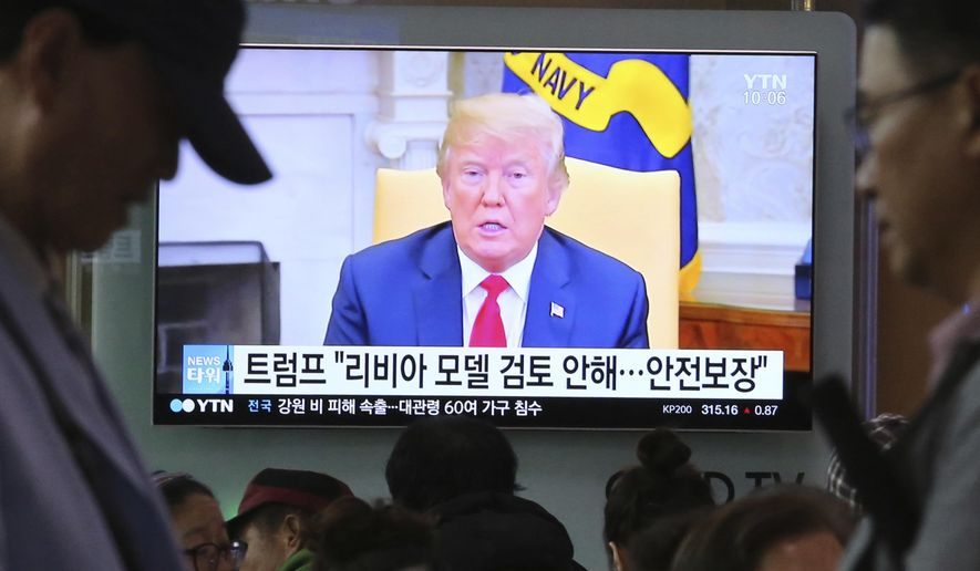 """A TV screen shows file footage of U.S. President Donald Trump during a news program at the Seoul Railway Station in Seoul, South Korea, Friday, May 18, 2018. North Korea strongly criticized South Korea over ongoing U.S.-South Korean military exercises on Thursday and said it will not return to talks with its rival until Seoul resolves its grievances. The signs read: """" Trump is not considering a so-called Libya model. """" (AP Photo/Ahn Young-joon)"""