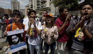 "People shout ""Freedom for prisoners"" outside the political police SEBIN headquarters and jail in Caracas, Venezuela, Thursday, May 17, 2018. Second from left is David Sosa, who was held at SEBIN along with ex-mayor Daniel Ceballos and American citizen Joshua Holt. The Utah man has been imprisoned in Venezuela for two years without a trial is making an emotional plea for Americans' help getting out of a Caracas jail. (AP Photo/Fernando Llano)"
