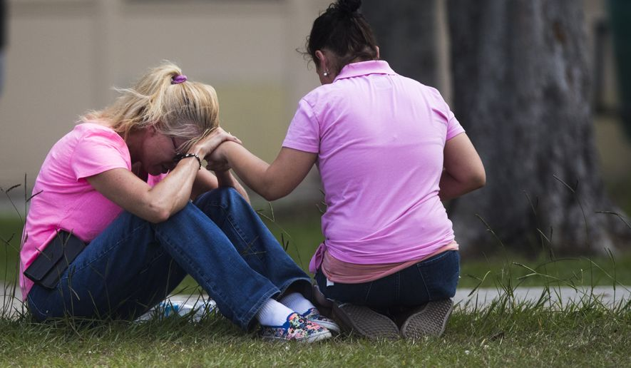 Two women pray outside the family reunification site following a shooting at Santa Fe High School on Friday, May 18, 2018, in Santa Fe, Texas.  (Marie D. De Jesus /Houston Chronicle via AP)