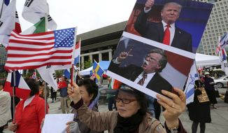 A protester in Seoul held portraits of President Trump and National Security Adviser John R. Bolton during a rally Friday supporting the U.S. policy to put steady pressure on North Korea. (Associated Press/File)