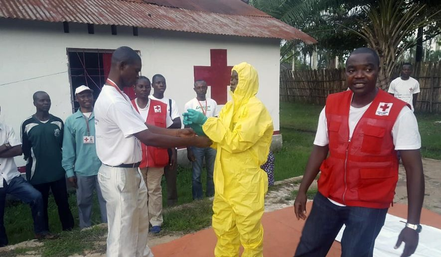 In this photo taken Monday, May 14, 2018, members of a Red Cross team don protective clothing before heading out to look for suspected victims of Ebola, in Mbandaka, Congo. (Karsten Voigt/International Federation of Red Cross and Red Crescent Societies via AP) ** FILE **