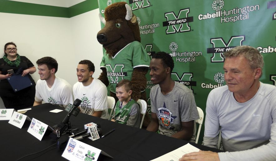 "Thundering Herd fan Calvin Fields, center, 8, of Kenova, signs a letter of intent with Marshall's basketball team through the Team IMPACT organization Wednesday, May 16, 2018, in Huntington W.V. Brentney Fields said her son was born and raised as a Marshall fan. ""He has had so much fun this last season, and for him to continue to get to do this and continue to hang out with the team, it's been amazing to him,"" she said. ""They treat him just like one of the guys. They mess with him and they play around with him. They don't treat him any different than any other member of the team, and that's amazing.""  (Lori Wolfe/The Herald-Dispatch via AP)"