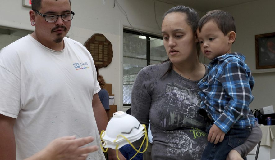 Lindsey Magnani, center, her finance Elroy Rodrigues, left, and their children, Kahele, right, and Kayden, not shown, pick up respirators to help protect against ash from Kilauea volcano, Thursday, May 17, 2018, in Volcano, Hawaii. Free respirators were being handed out to communities around the volcano after it erupted early Thursday, sending a plume of ash about 30,000 feet into the air. (AP Photo/Caleb Jones)