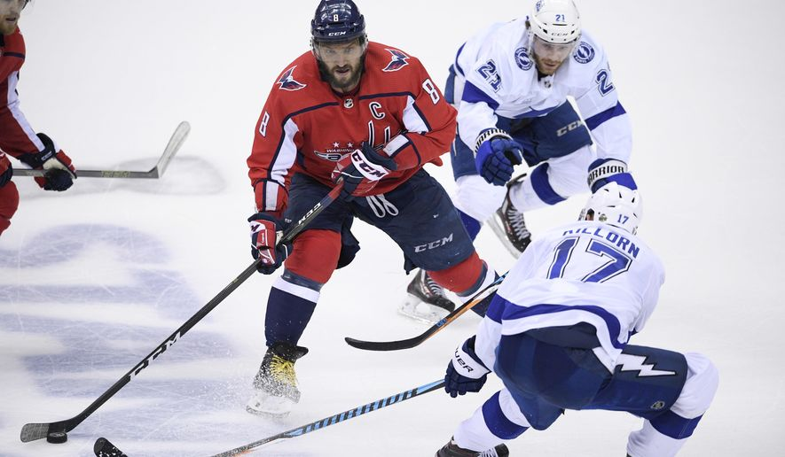 Washington Capitals left wing Alex Ovechkin (8), of Russia, skates with the puck against Tampa Bay Lightning left wing Alex Killorn (17) and center Brayden Point (21) during the third period of Game 4 of the NHL hockey Eastern Conference finals Thursday, May 17, 2018, in Washington. The Lightning won 4-2. (AP Photo/Nick Wass)