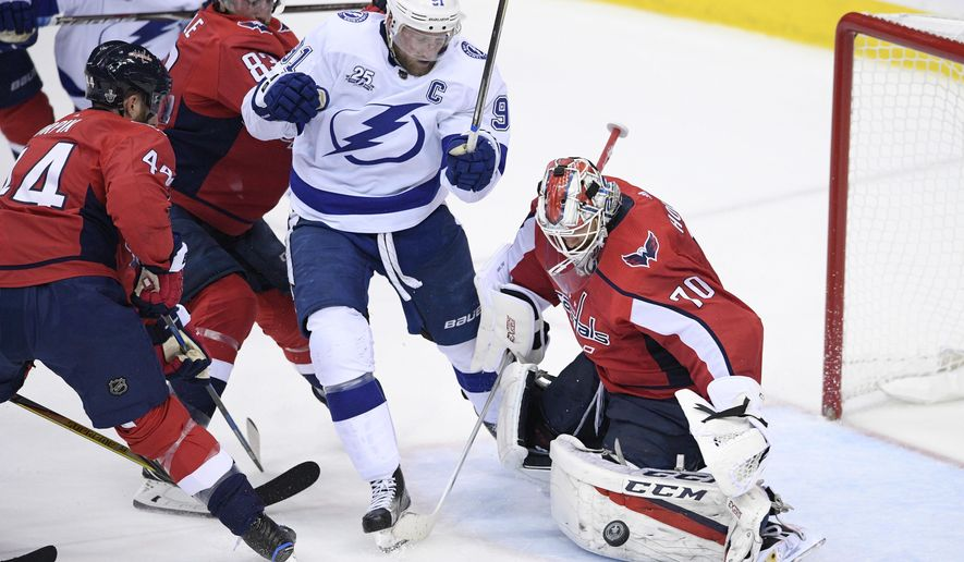 Washington Capitals goaltender Braden Holtby (70) stops the puck next to Tampa Bay Lightning center Steven Stamkos (91) during the second period of Game 4 of the NHL hockey Eastern Conference finals Thursday, May 17, 2018, in Washington. Also seen is Capitals defenseman Brooks Orpik (44). (AP Photo/Nick Wass) ** FILE **