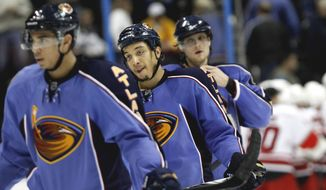 FILE - In this Feb. 13, 2011, file photo, Atlanta Thrashers right wing Anthony Stewart, center, skates off the ice with teammates Evander Kane, left, and Nik Antropov after losing 3-2 to the Carolina Hurricanes in an NHL hockey game in Atlanta. Down in Atlanta, hockey fans are still bitter about the way they lost the Thrashers seven years ago to Winnipeg, a move that deprived this city of its second team and probably any chance to ever again be associated with the NHL.  (AP Photo/David Goldman)