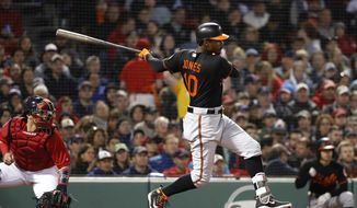Baltimore Orioles' Adam Jones follows through on a two-run single against the Boston Red Sox during the fourth inning of a baseball game at Fenway Park in Boston Friday, May 18, 2018.(AP Photo/Winslow Townson)