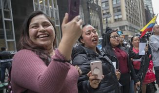 Demonstrator sing along as the Mariachi Tapatio de Alvaro Paulino band performs during a demonstration across the street from the building that once housed the office space of Aaron Schlossberg, Friday, May 18, 2018, in New York. Schlossberg, a lawyer who was caught on video ranting against Spanish-speaking restaurant workers has been kicked out of his office space and faces a complaint from two elected officials. (AP Photo/Mary Altaffer)