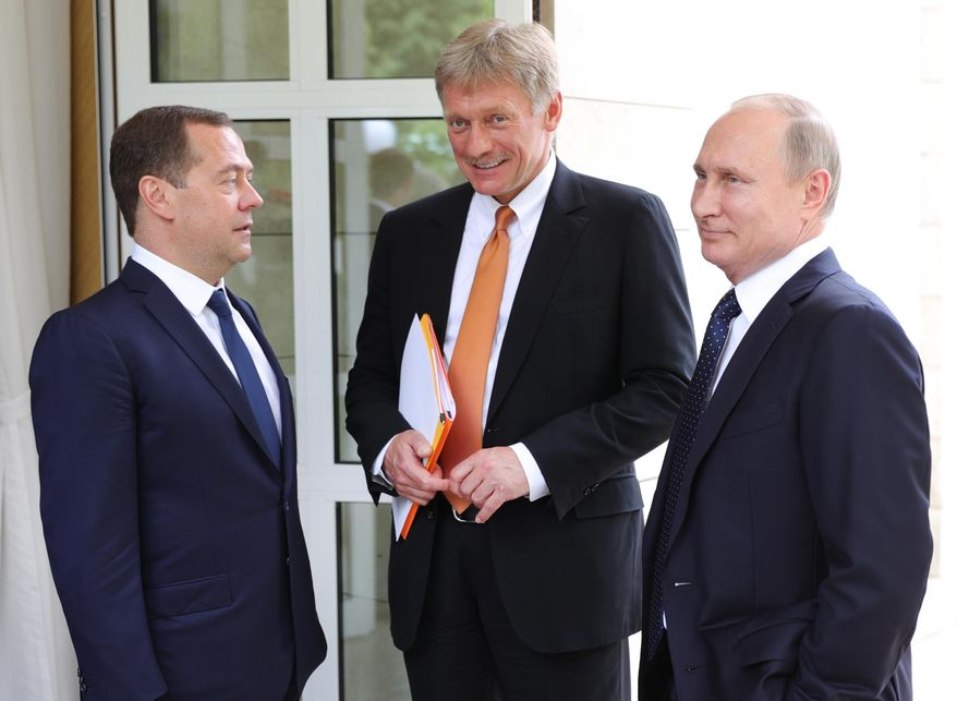 Russian President Vladimir Putin, right, presidential spokesman Dmitry Peskov, center, Russian Prime Minister Dmitry Medvedev, left, seen in the Russian Black Sea resort of Sochi, Russia, Friday, May 18, 2018. (Mikhail Klimentyev, Sputnik, Kremlin Pool Photo via AP) ** FILE **
