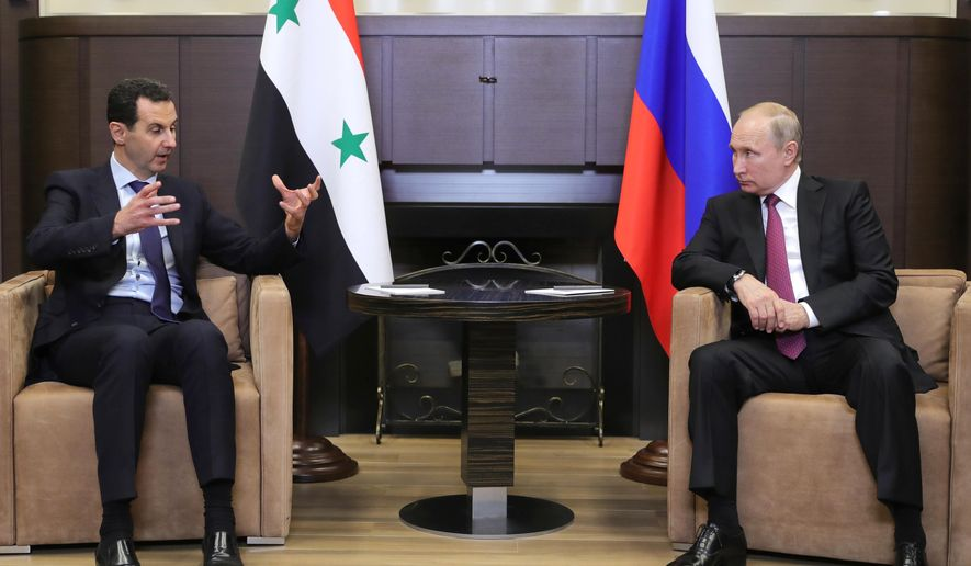 """Russian President Vladimir Putin, right, listens to Syrian President Bashar al-Assad during their meeting in the Black Sea resort of Sochi, Russia, Thursday, May 17, 2018. A transcript of Thursday's meeting released by the Kremlin quoted Assad as saying that Syria is making progress in fighting """"terrorism,"""" which """"opens the door to the political process."""" (Mikhail Klimentyev, Sputnik, Kremlin Pool Photo via AP)"""