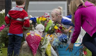 A girl leans over bouquets of flowers to blow a kiss at a memorial in front of East Brook Middle School, Friday, May 18, 2018, in Paramus, N.J. Investigators are combing through evidence seeking answers to why a school bus carrying 45 fifth-graders and teachers on a field trip collided with a dump truck on Thursday on a New Jersey highway, killing a student and teacher and sending dozens to area hospitals. (AP Photo/Mark Lennihan)