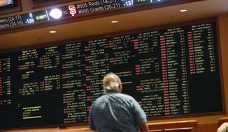 FILE - In this Monday, May 14, 2018 file photo, betting odds are displayed on a board in the sports book at the South Point hotel and casino in Las Vegas. A new poll finds that half of Americans approve of legal sports betting. The Fairleigh Dickinson University poll conducted shortly before the U.S. Supreme Court cleared the way for states to legalize sports betting found that 50 percent of Americans favor it, with 37 percent opposed. (AP Photo/John Locher, File)