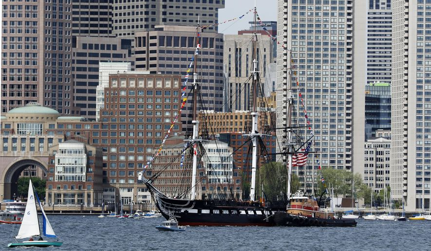 """The USS Constitution glides through Boston Harbor past the city skyline on a cruise to honor Vietnam veterans, Friday, May 18, 2018, in Boston. The U.S. Navy vessel known as """"Old Ironsides"""" is the world's oldest commissioned warship still afloat. (AP Photo/Bill Sikes)"""