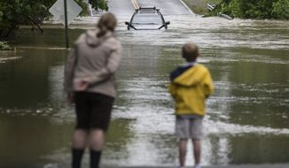 Barrett Maddox and her son, Brighton, 6, check out a vehicle stuck in floodwater near the intersection of Gayton Road and Cedarbluff Drive in Herico, Va., on Friday, May 18, 2018. Flash flooding is affecting parts of central Virginia, and downed trees have caused thousands of power outages. (Daniel Sangjib/Richmond Times-Dispatch via AP)