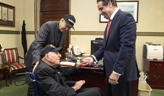 In this photo provided by the Office of the Governor of New York, Governor Andrew M. Cuomo, right, shakes hands with World War II veteran Sidney Walton at the Capitol in Albany, N.Y., Friday, May 18, 2018. The 99-year-old World War II veteran who regretted skipping the chance to meet some of the nation's last Civil War veterans in 1940 is on a mission to visit all 50 states so people who've never met a WWII vet can finally meet one. Standing at left is Walton's son, Paul Walton. (Mike Groll/Office of Governor Andrew M. Cuomo via AP)