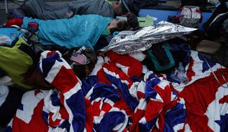 Royal fans sleep in their sleeping bags to hold a spot at the front of barriers for the carriage procession outside Windsor Castle, ahead of the wedding ceremony of Prince Harry and Meghan Markle at St. George's Chapel in Windsor, near London, England, Saturday, May 19, 2018. (AP Photo/Frank Augstein)