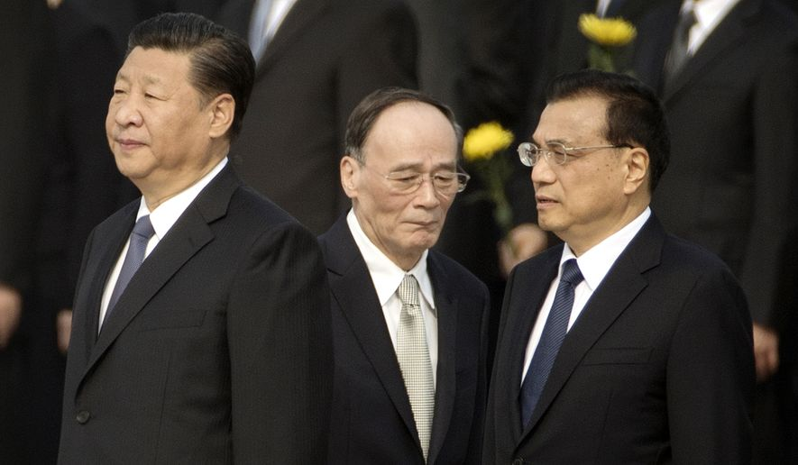FILE - In this Sept. 30, 2017 file photo, Chinese President Xi Jinping, left, Politburo Standing Committee member Wang Qishan, center, and Chinese Premier Li Keqiang attend a ceremony marking Martyrs' Day at Tiananmen Square in Beijing. Chinese President Xi Jinping is increasingly turning to friend and trusted confidant Wang Qishan to help guide the country's foreign relations as he prepares for a potentially bruising trade fight with the U.S. and competition for leadership in Asia. (AP Photo/Mark Schiefelbein, File)
