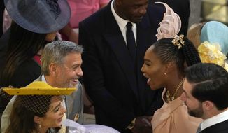 George Clooney, center left, greets Serena Williams in St. George's Chapel at Windsor Castle for the wedding of Prince Harry and Meghan Markle in Windsor, England on Saturday, May 19, 2018. In the foreground are Amal Clooney, left, and Alexis Ohanian. At background center is Idris Elba. (Owen Humphreys/PA via AP)