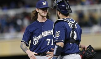Milwaukee Brewers' pitcher Josh Hader, left, celebrates with catcher Manny Pina after the Brewers defeated the Minnesota Twins 5-4 in a baseball game Saturday, May 19, 2018, in Minneapolis. Hader picked up the win. (AP Photo/Jim Mone)