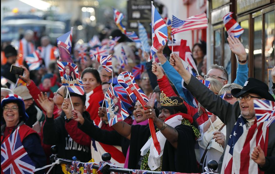 Royal fans waiting at the barriers cheer ahead of the wedding ceremony of Prince Harry and Meghan Markle at St. George's Chapel in Windsor Castle in Windsor, near London, England, Saturday, May 19, 2018. (AP Photo/Frank Augstein)