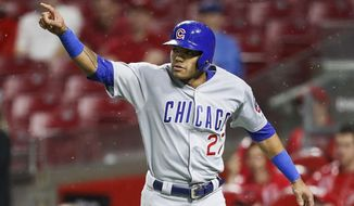 Chicago Cubs' Addison Russell celebrates after scoring on an RBI double by Kyle Schwarber off Cincinnati Reds starting pitcher Homer Bailey during the fifth inning of a baseball game Friday, May 18, 2018, in Cincinnati. (AP Photo/John Minchillo)