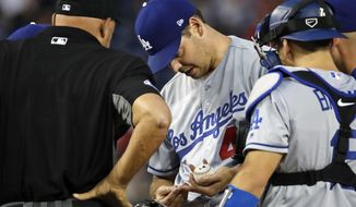 Los Angeles Dodgers starting pitcher Rich Hill, center, looks at his finger with home plate umpire Kerwin Danley and others, during the first inning of the second baseball game of a doubleheader against the Washington Nationals at Nationals Park, Saturday, May 19, 2018, in Washington. Hill was relieved after throwing two pitches. (AP Photo/Alex Brandon)