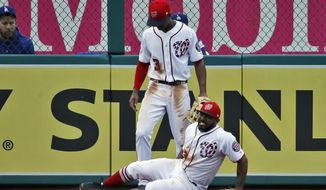 Washington Nationals left fielder Howie Kendrick reacts after an injury, with center fielder Michael Taylor standing behind, during the eighth inning of the first baseball game of a doubleheader against the Los Angeles Dodgers at Nationals Park, Saturday, May 19, 2018, in Washington. The Dodgers won the first game 4-1. (AP Photo/Alex Brandon)