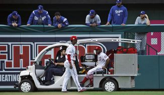 Washington Nationals center fielder Michael Taylor, left, walks away as left fielder Howie Kendrick is taken away on the cart after an injury, as the Los Angeles Dodgers bullpen watches from above, during the eighth inning of the first baseball game of a doubleheader at Nationals Park, Saturday, May 19, 2018, in Washington. The Dodgers won the first game 4-1. (AP Photo/Alex Brandon) ** FILE **