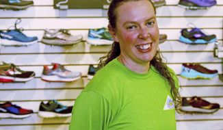 In this May 10, 2018, photo, run manager Stacy Fisk poses in the running department at Goldstream Sports where she works in Fairbanks, Alaska. Three months after Fisk moved to Fairbanks, the run manager position opened up, a perfect job for Fisk, a former collegiate runner. The 36-year-old Fisk has an impressive running resume from Mars Hill College, a Division II school in North Carolina. (Eric Engman/Fairbanks Daily News-Miner via AP)