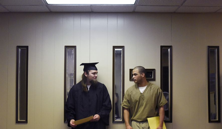In this Thursday, May 10, 2018 photo, Kameron Reynolds, left, and Fabian Ramos speak to each other after their graduation ceremony at the South Dakota State Penitentiary in Sioux Falls, S.D. Twenty inmates at the South Dakota State Penitentiary in Sioux Falls have earned their general equivalency diplomas. (Loren Townsley/The Argus Leader via AP)