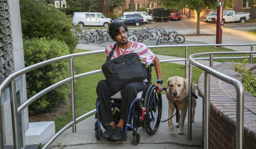 In this April 18, 2018 photo, Ronny Ahmed, 25, and service dog Marino use a wheelchair ramp to enter the Florida State University's library in Tallahassee, Fla. Ahmed, who is a student at FSU, was left paralyzed from the waist down after being shot twice while taking a study break outside this library (Alessandra Da Pra/Tampa Bay Times via AP)