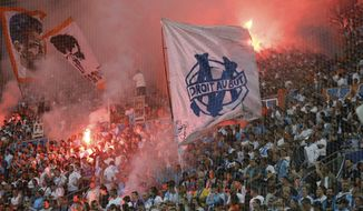 Marseille supporters burn flares and hold flags during the League One soccer match between Marseille and Amiens at the Velodrome stadium, in Marseille, southern France, Saturday, May 19, 2018. (AP Photo/Claude Paris)