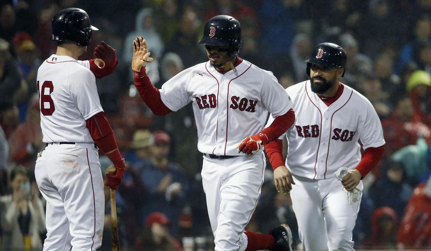 Boston Red Sox's Mookie Betts, center, celebrates his two-run home run that also drove in Sandy Leon, right, during the fifth inning of a baseball game against the Baltimore Orioles in Boston, Saturday, May 19, 2018. (AP Photo/Michael Dwyer)
