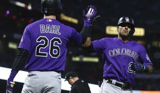 Colorado Rockies' Ian Desmond, right, celebrates with David Dahl (26) after hitting a three-run home run off San Francisco Giants' Derek Holland in the fourth inning of a baseball game Friday, May 18, 2018, in San Francisco. (AP Photo/Ben Margot)