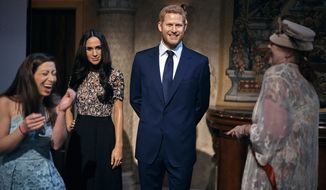People take pictures of wax sculptures of Meghan Markle, second left, and Prince Harry, second right, during a viewing party of the royal wedding of Meghan Markle and Prince Harry of Wales, at the Madame Tussauds wax museum on Saturday, May 19, 2018, in New York. From pubgoers in pajamas to merrymakers in finery at a posh hotel, Americans cheered and teared up Saturday as they watched Meghan Markle marry Prince Harry in a royal wedding with trans-Atlantic resonance (AP Photo/Andres Kudacki)