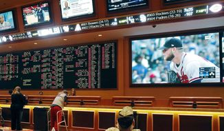 FILE - In this Monday, May 14, 2018 file photo, people make bets in the sports book area of the South Point Hotel and Casino in Las Vegas. Those who deal with compulsive gambling are worried that a rapid expansion of sports betting in the U.S. could cause more people to develop gambling problems. The U.S. Supreme Court on Monday cleared the way for states to legalize sports betting. (AP Photo/John Locher, File)