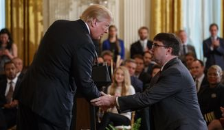 President Donald Trump shakes hands with acting Department of Veterans Affairs Secretary Robert Wilkie after announcing he will nominate him to lead the department during an event on prison reform in the East Room of the White House, Friday, May 18, 2018, in Washington. (AP Photo/Evan Vucci)