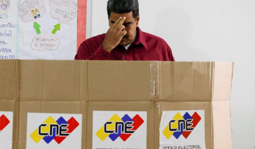 Venezuela's President Nicolas Maduro crosses himself before voting in presidential elections in Caracas, Venezuela, on Sunday. Mr. Maduro is seeking a second term. (ASSOCIATED PRESS)