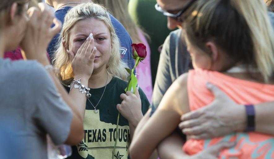 A woman wipes away tears during a prayer vigil following a shooting at Santa Fe High School in Santa Fe, Texas, on Friday, May 18, 2018. Seventeen-year-old Dimitrios Pagourtzis is charged with capital murder in the deadly shooting rampage. (Stuart Villanueva The Galveston County Daily News via AP)