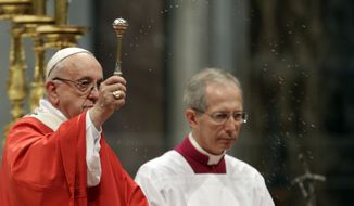 Pope Francis asperges holy water as he celebrates a Pentecost mass in St. Peter's Basilica, at the Vatican, Sunday, May 20, 2018. (AP Photo/Gregorio Borgia)
