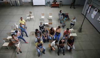 People wait their turn to vote during the presidential election in Caracas, Venezuela, Sunday, May 20, 2018. Amidst hyperinflation and shortages of food and medicine, President Nicolas Maduro is seeking a second, six-year term in an election that a growing chorus of foreign governments refuse to recognize after key opponents were barred from running.  (AP Photo/Ariana Cubillos)