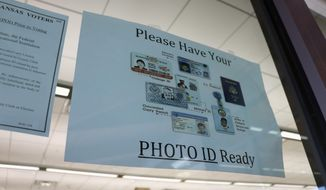 In this May 7, 2018, photo, a sign is posted above the check-in station for an early voting precinct at the Roosevelt Thompson Library in Little Rock, Ark., warning voters that they will be asked to show an identification card. Democratic and Republican voters on Tuesday, May 22, 2018, will choose nominees for the November general election, and all voters are eligible to vote in non-partisan court and prosecuting attorney races. (AP Photo/Kelly P. Kissel)