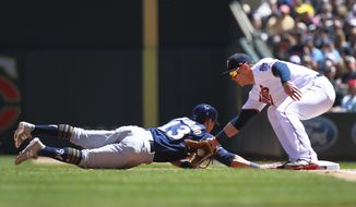 Minnesota Twins first baseman Logan Morrison, right, tags out Milwaukee Brewers' Tyler Saladino (13) in the third inning of a baseball game Sunday, May 20, 2018, in Minneapolis. (AP Photo/Andy Clayton-King)