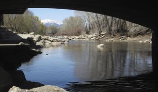 In this April 25, 2018 photo, the Arkansas River flows under a bridge in Salida, Colo., with the snow-covered Sawatch Range mountains in the background. Despite a severe drought across the Southwestern United States, there should be plenty of water this year for rafters and anglers in the Arkansas, one of the nation's most popular mountain rivers. State and federal officials say water from melting snow will surge down the river thanks to a surprisingly wet winter in the towering peaks of the Sawatch Range where the river begins. (AP Photo/Dan Elliott)