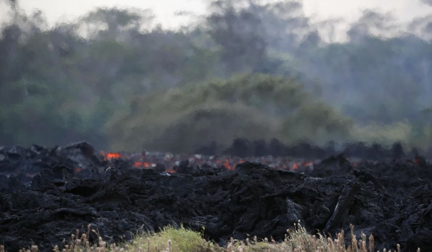 Lava flows toward the ocean near Pahoa, Hawaii Saturday, May 19, 2018. Two fissures that opened up in a rural Hawaii community have merged to produce faster and more fluid lava. Scientists say the characteristics of lava oozing from fissures in the ground has changed significantly as new magma mixes with decades-old stored lava. (AP Photo/Jae C. Hong)