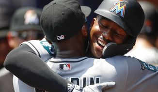 Miami Marlins Lewis Brinson reacts with Cameron Maybin after hitting a grand slam in the fourth inning of a baseball game against the Atlanta Braves, Sunday, May 20, 2018, in Atlanta. (AP Photo/Todd Kirkland)