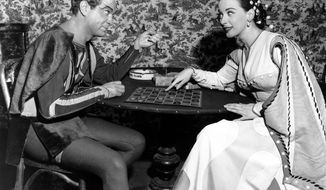 """FILE - In this Dec. 25, 1949, file photo, Alfred Drake, left, and Patricia Morison, costarring in the musical """"Kiss Me Kate,"""" play checkers backstage at the New Century Theatre in New York. Broadway and Hollywood star Patricia Morison has died at age 103. Publicist Harlan Boll says Morison died of natural causes at her home in Los Angeles on Sunday, May 20, 2018. (AP Photo/File)"""