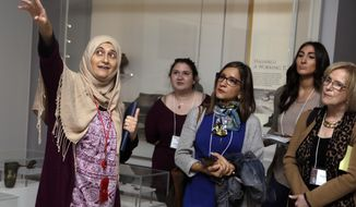 In this April 26, 2018 photo, Moumena Saradar, left, originally from Syria, guides visitors through the Middle East gallery at Penn Museum, in Philadelphia. The University of Pennsylvania Museum of Archaeology and Anthropology is in the midst of dramatic renovations, opening new galleries to showcase previously undisplayed items, telling the stories of those artifacts in more relatable ways and adding guides native to the parts of the world being showcased. (AP Photo/Jacqueline Larma)